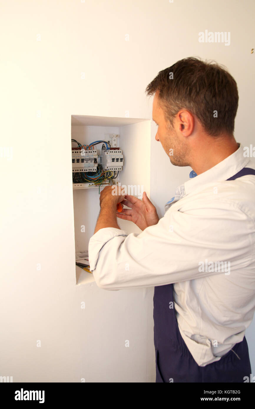 Electrician installing electric meter - Stock Image