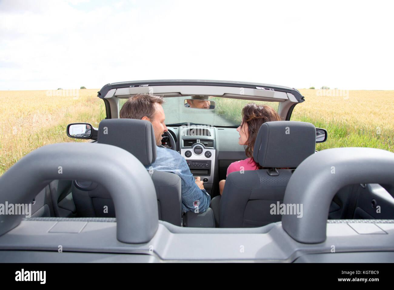 Couple riding convertible car - Stock Image