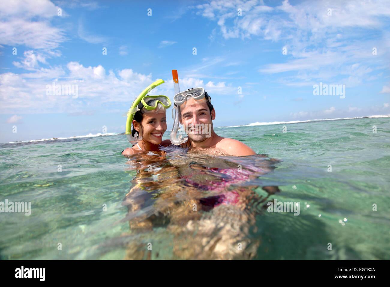 Portrait of happy couple doing snorkeling - Stock Image
