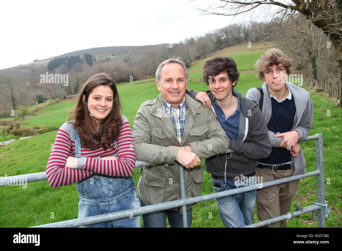 Adult man with teenagers in agricultural field - Stock Image