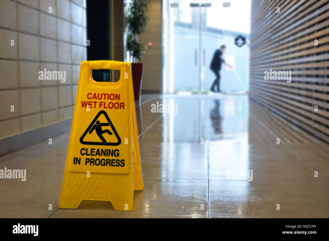 Slippery floor surface warning sign and symbol on a wet floor of unrecognizable building hallway. - Stock Image
