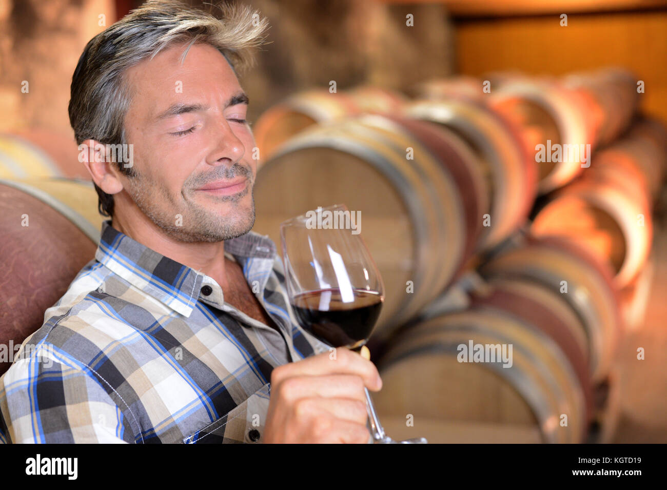 Winemaker enjoying the smell of red wine - Stock Image