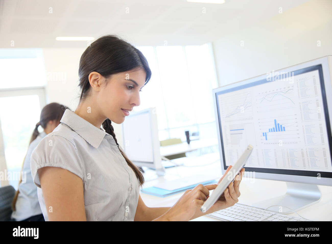 Young business girl working on digital tablet in office - Stock Image