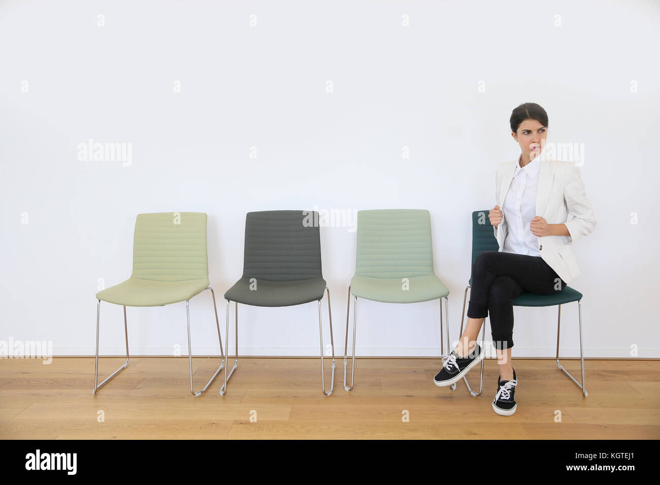 Woman in waiting room being serious - Stock Image