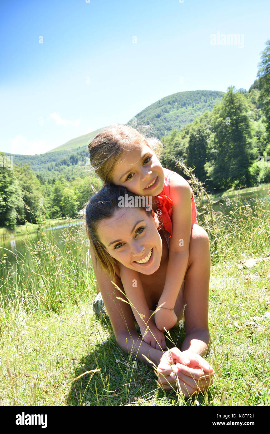 Portrait of happy mother and daughter laying by lake - Stock Image