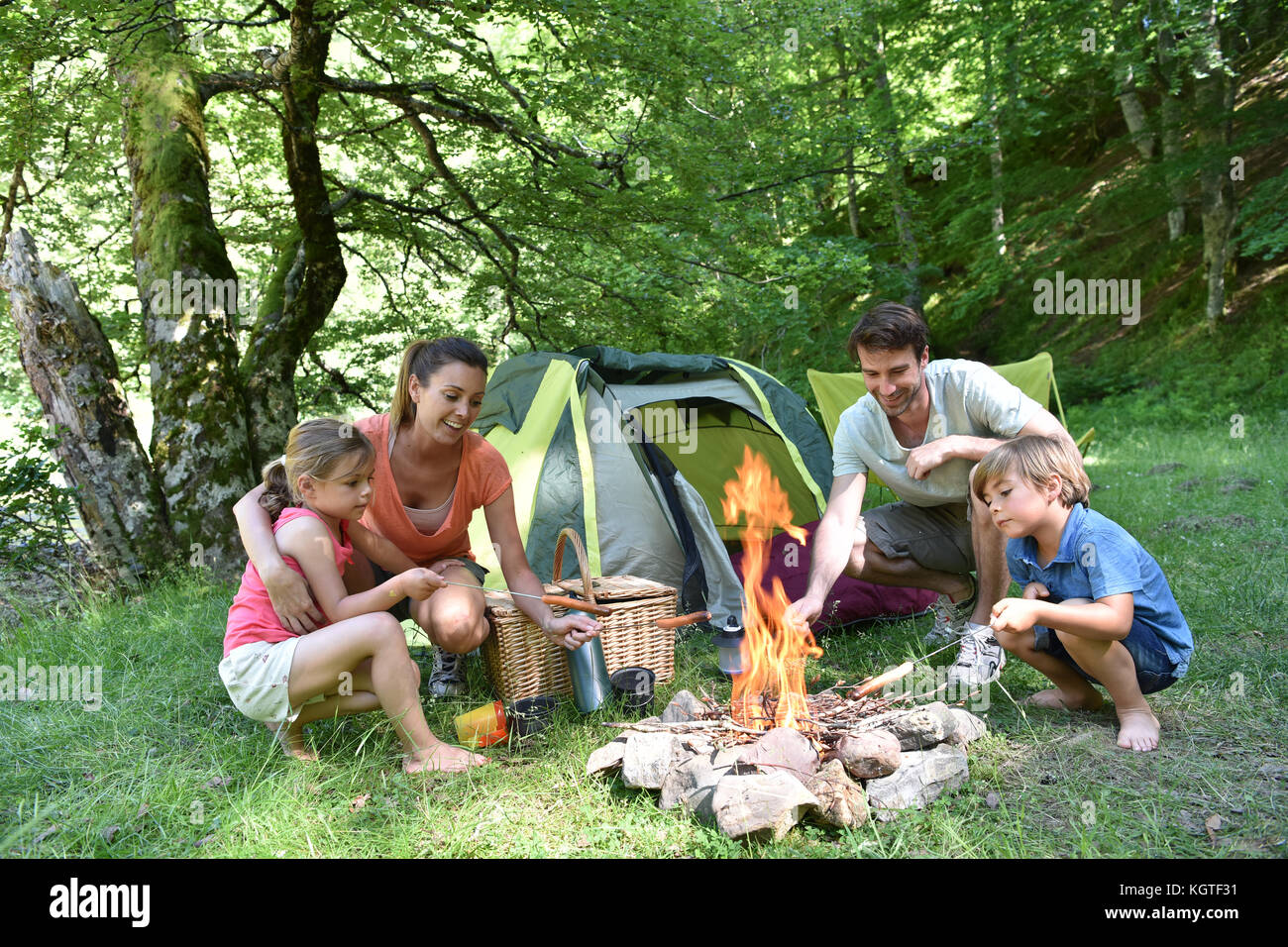Family camping and cooking sausages in campfire - Stock Image