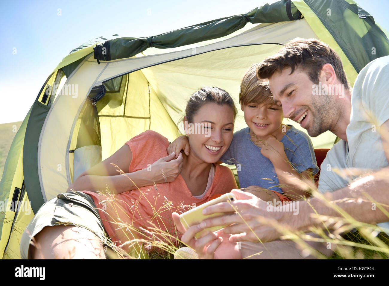 Family in camping tent playing with smartphone - Stock Image