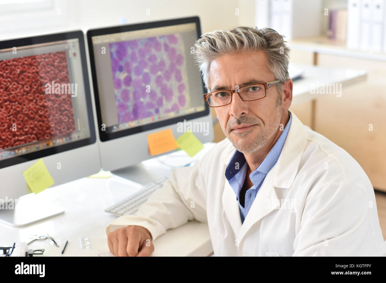 Portrait of microbiology scientist in office - Stock Image