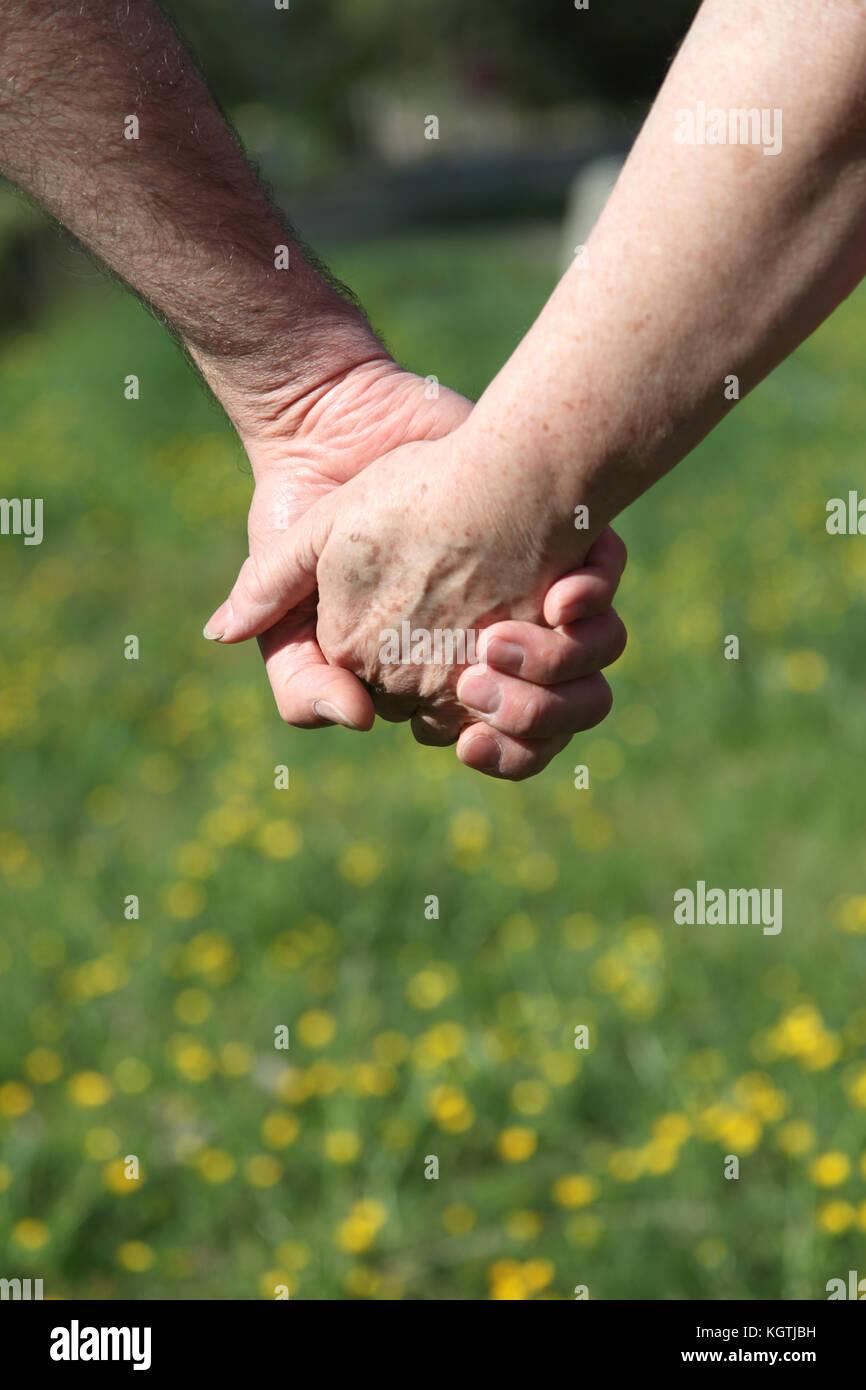 Closeup of senior couple holding hands Stock Photo