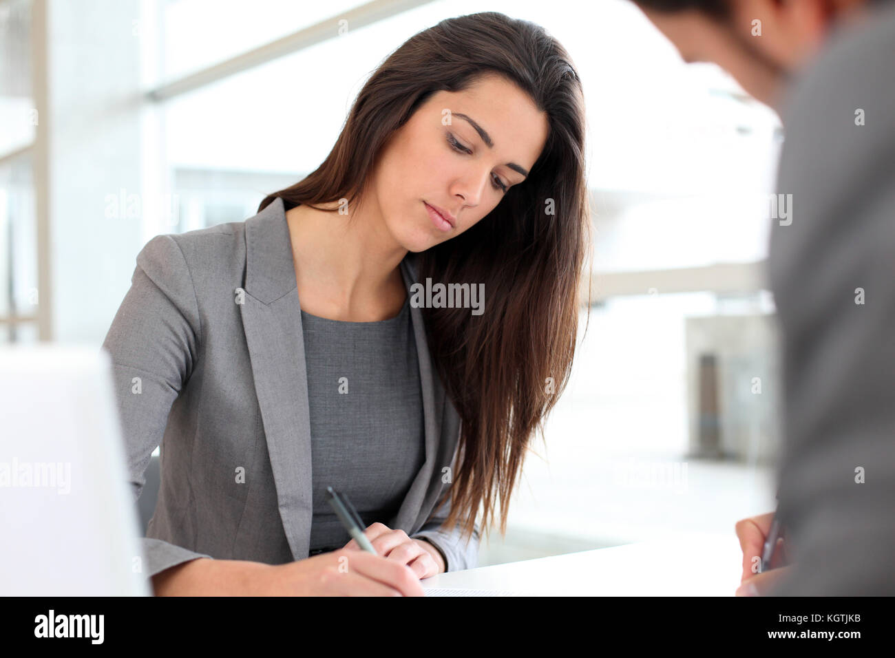 Businesswoman writing on document after meeting - Stock Image