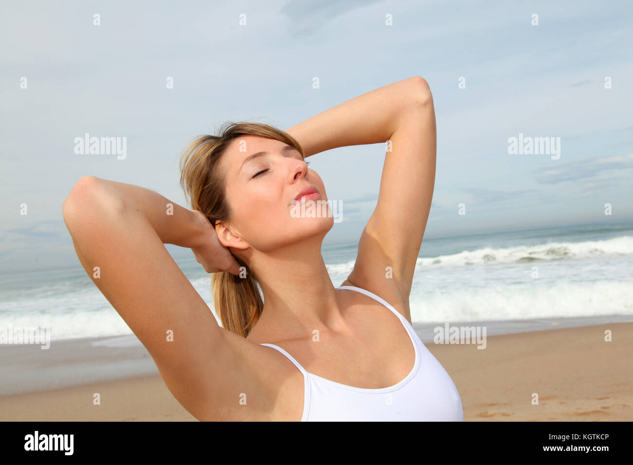 Beautiful woman breathing fresh air at the beach - Stock Image