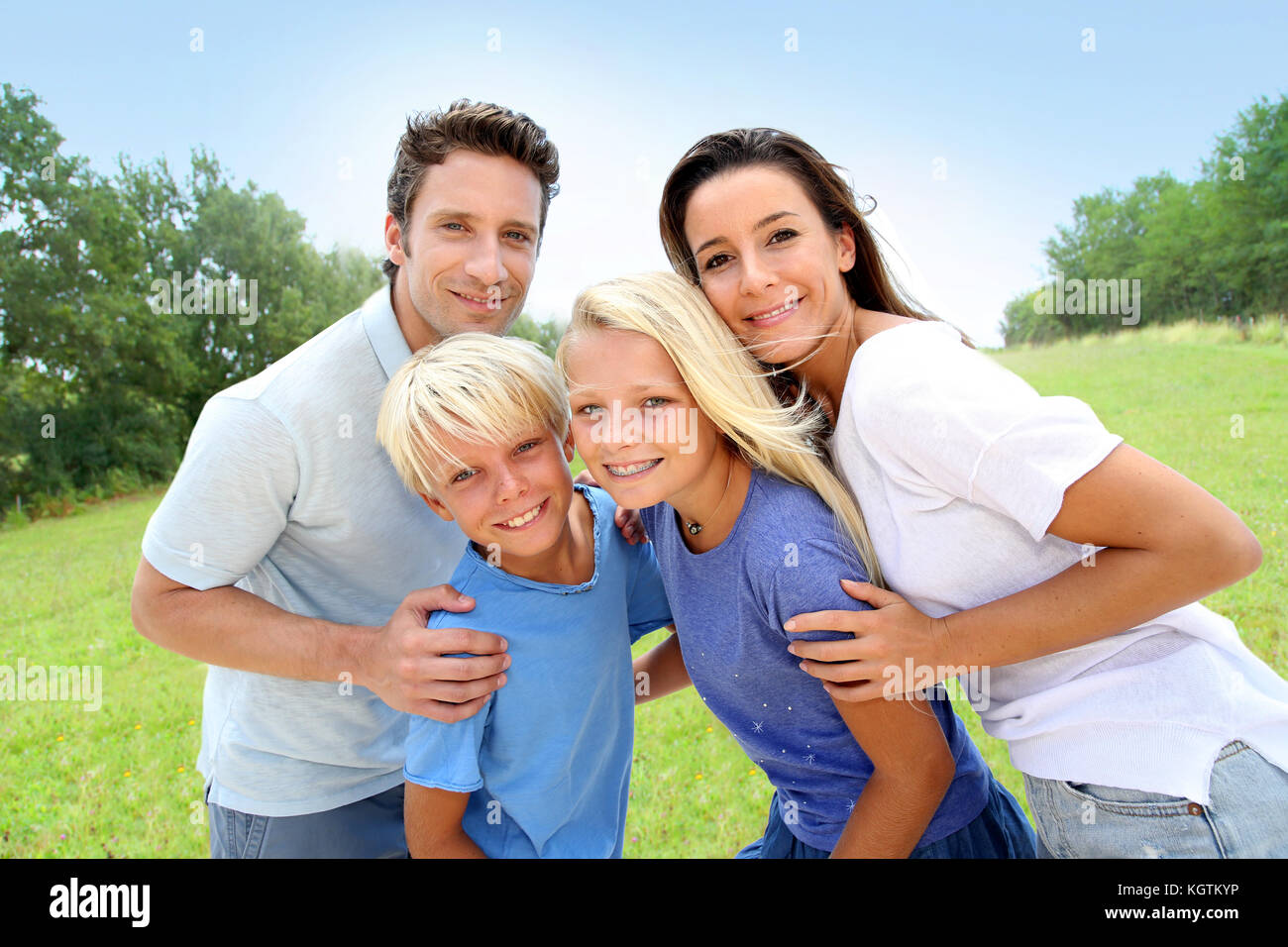 Portrait fo happy family standing in natural landscape - Stock Image