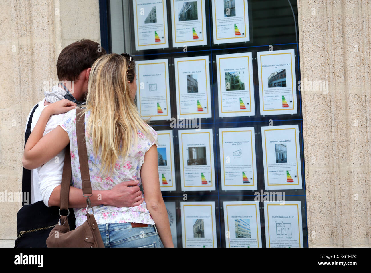 Couple looking at house-for-sale ads through shop window - Stock Image