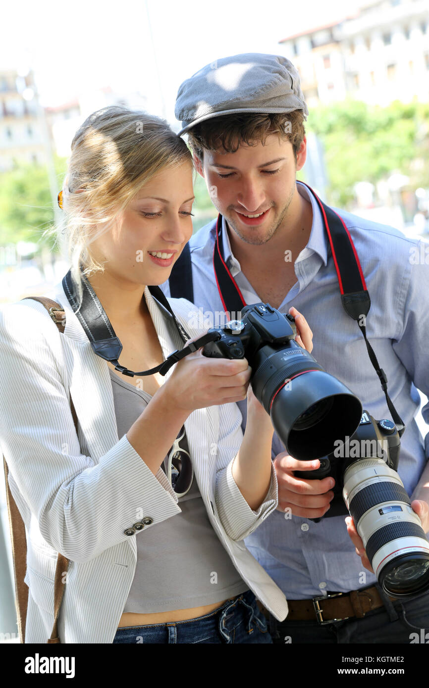 Couple of photographers looking at snapshots - Stock Image