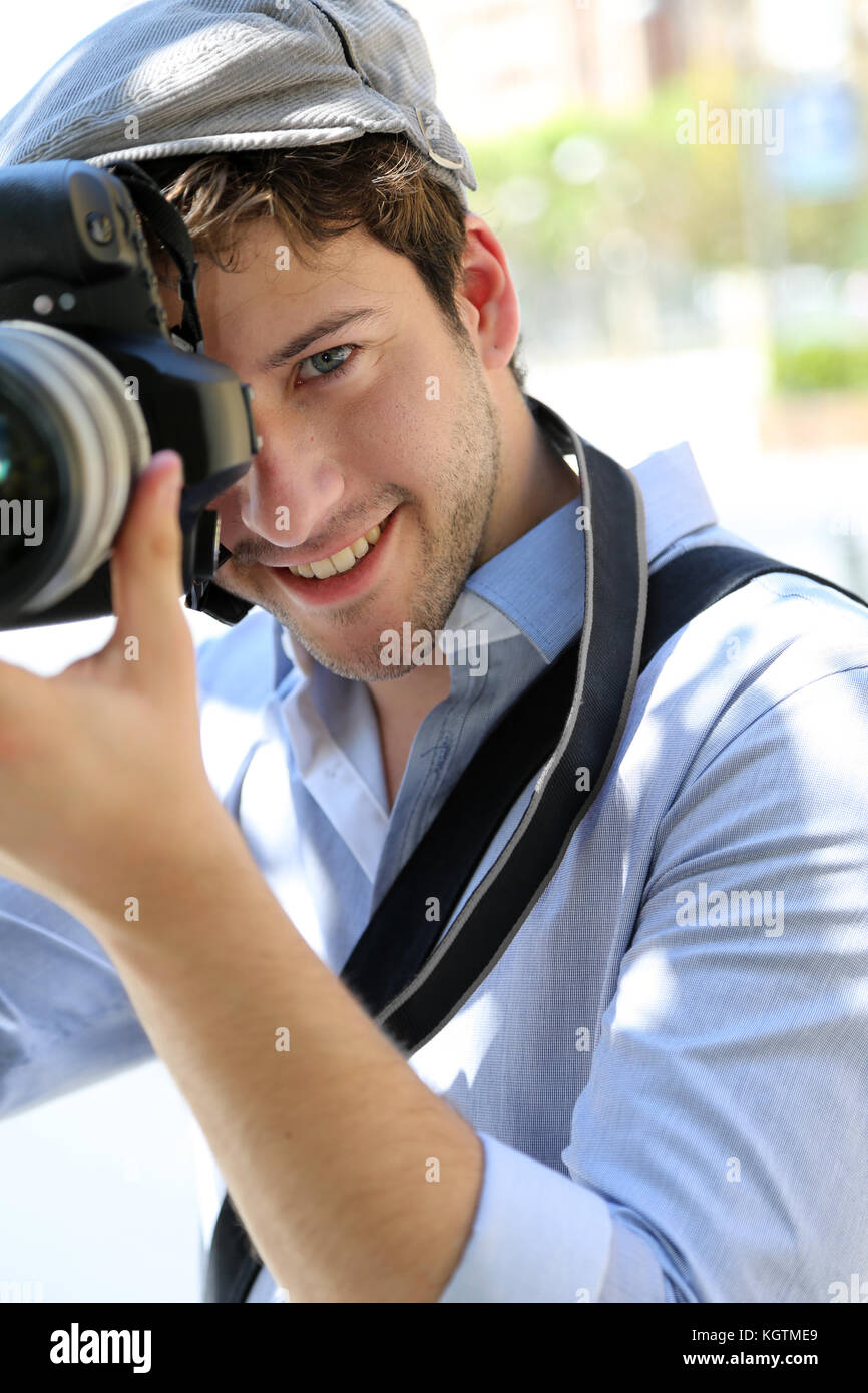 Portrait of young photographer holding camera - Stock Image