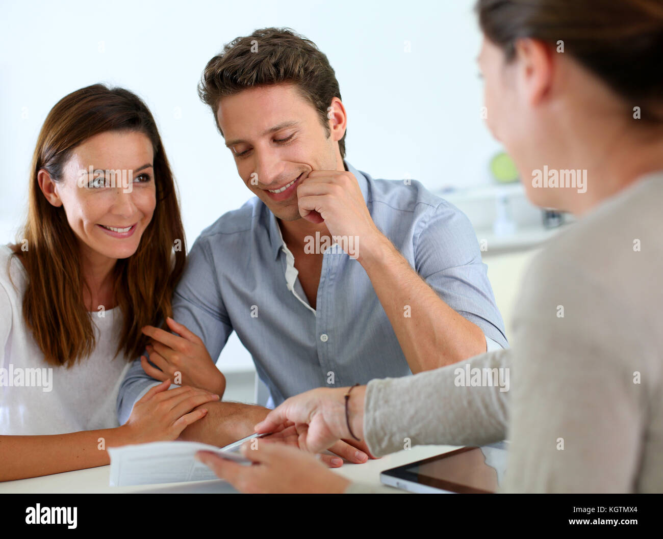 Future property owners reading terms of contract - Stock Image