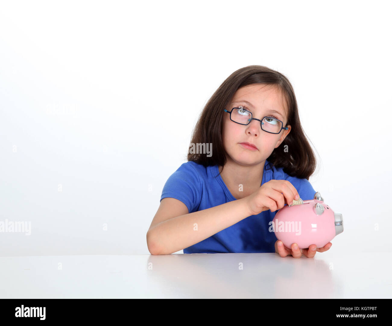 Little girl putting coin in piggybank - Stock Image