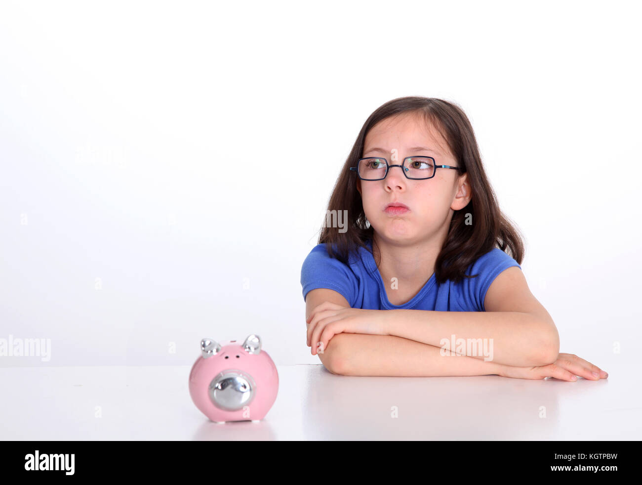 Little girl with bored look sitting by piggybank - Stock Image