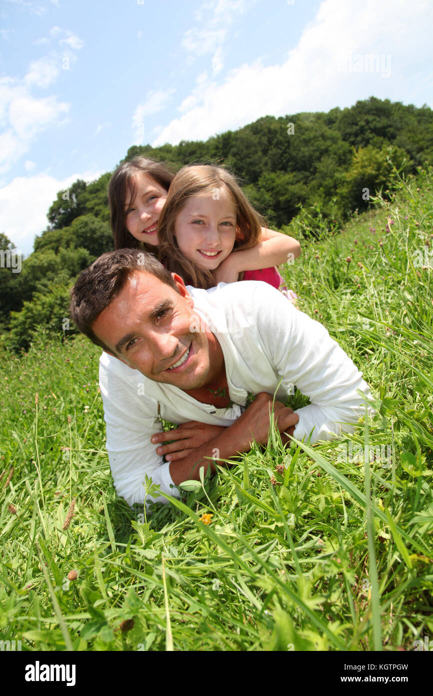 Man lying down in park with girls on his back - Stock Image