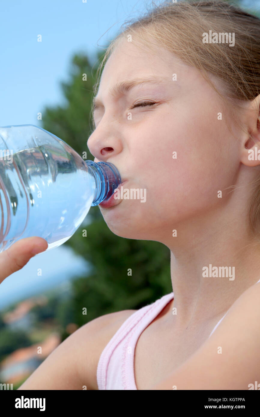 Portrait of young girl drinking water from bottle - Stock Image