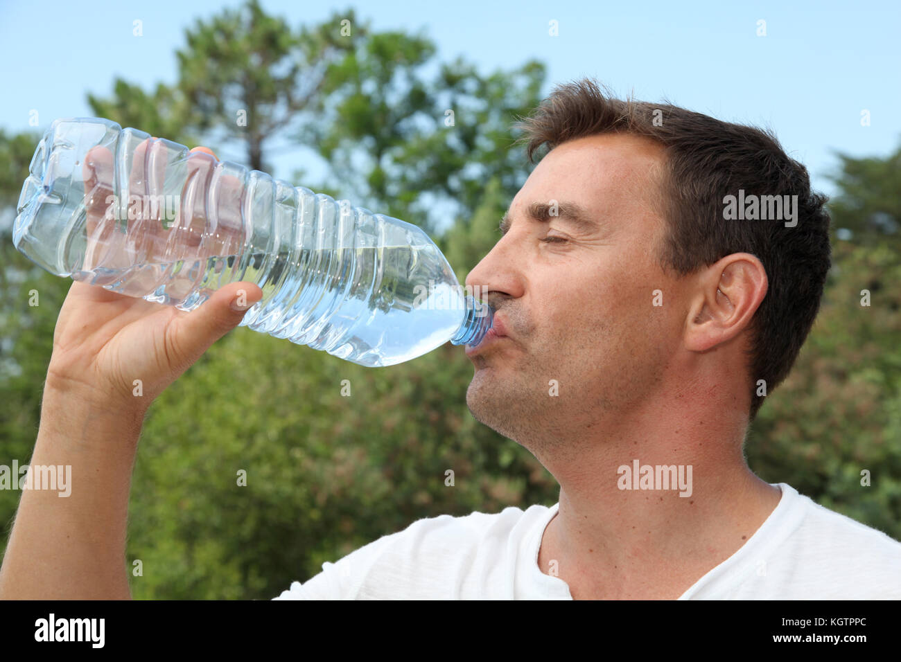 Man drinking water from bottle - Stock Image
