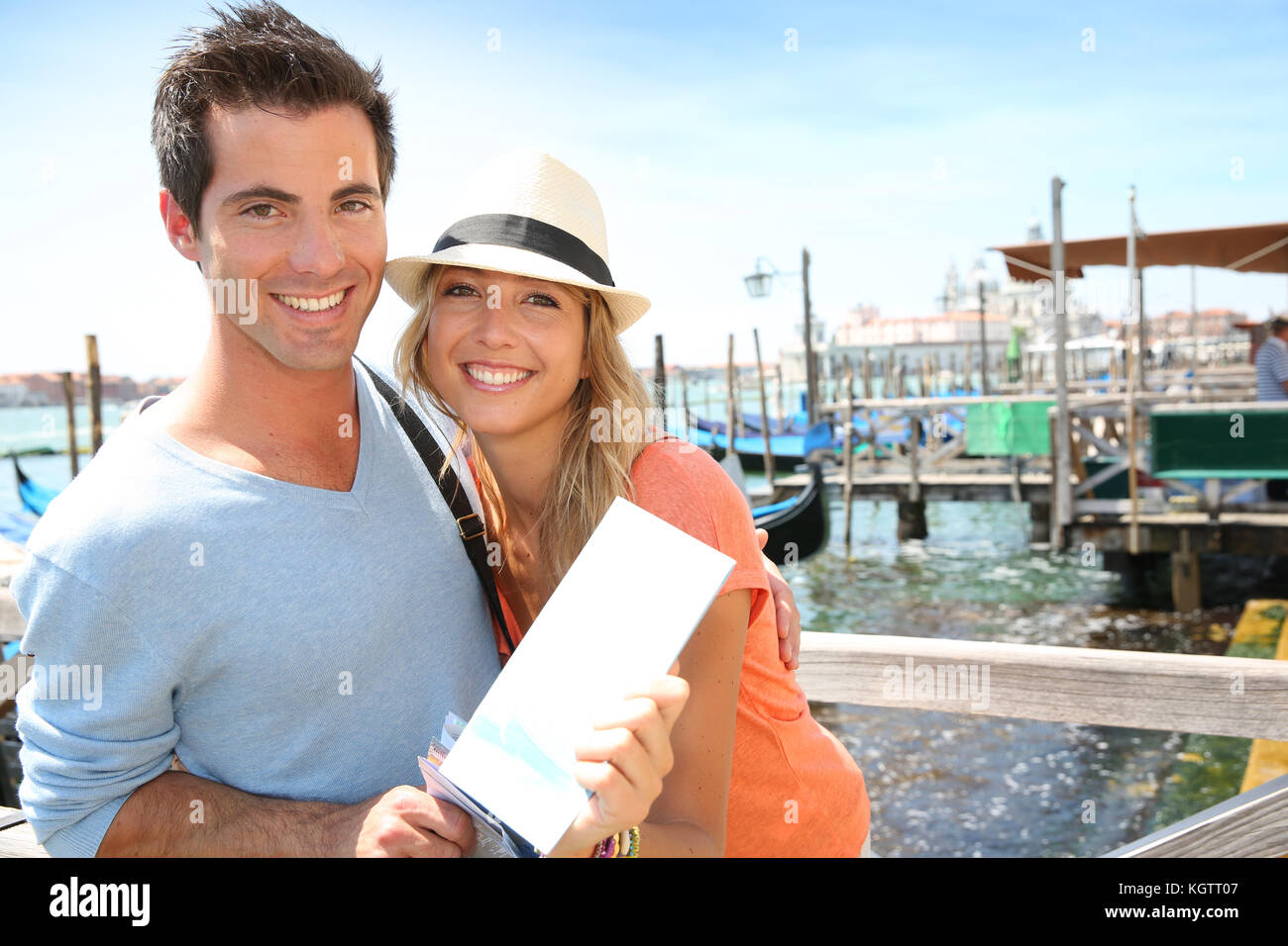 Cheerful couple in Venice showing tourist guide book - Stock Image