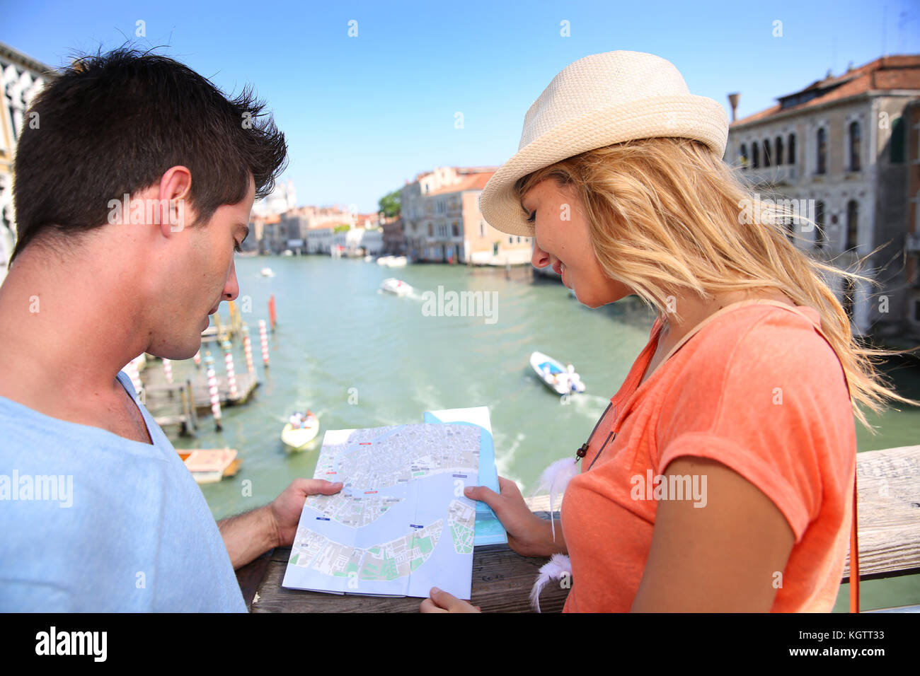 Couplelooking at map on the Academia Bridge in Venice, Italy Stock Photo