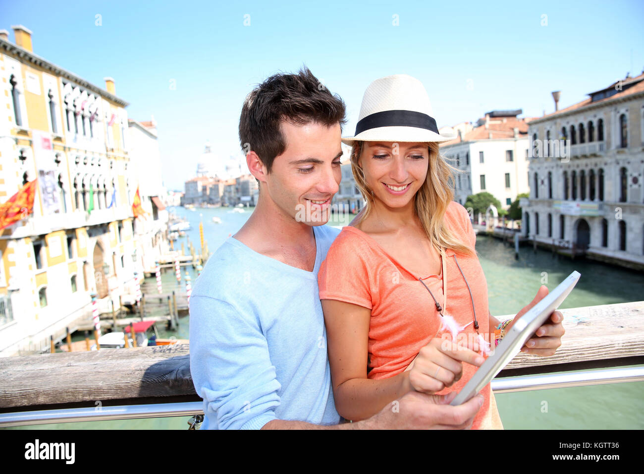 Couple using tablet on the Academia Bridge in Venice, Italy - Stock Image