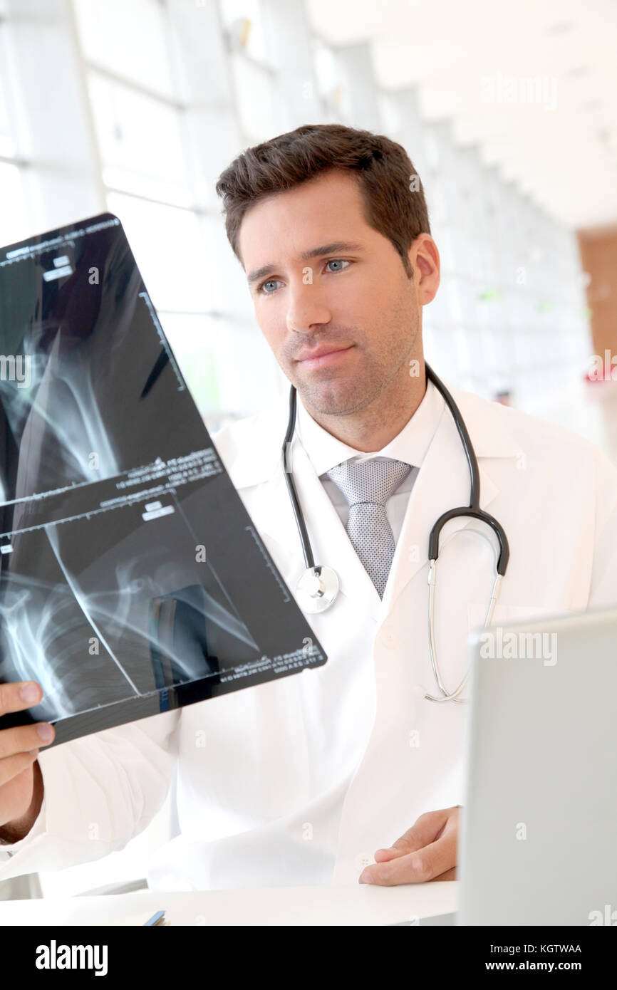 Portrait of young doctor checking X-Ray - Stock Image