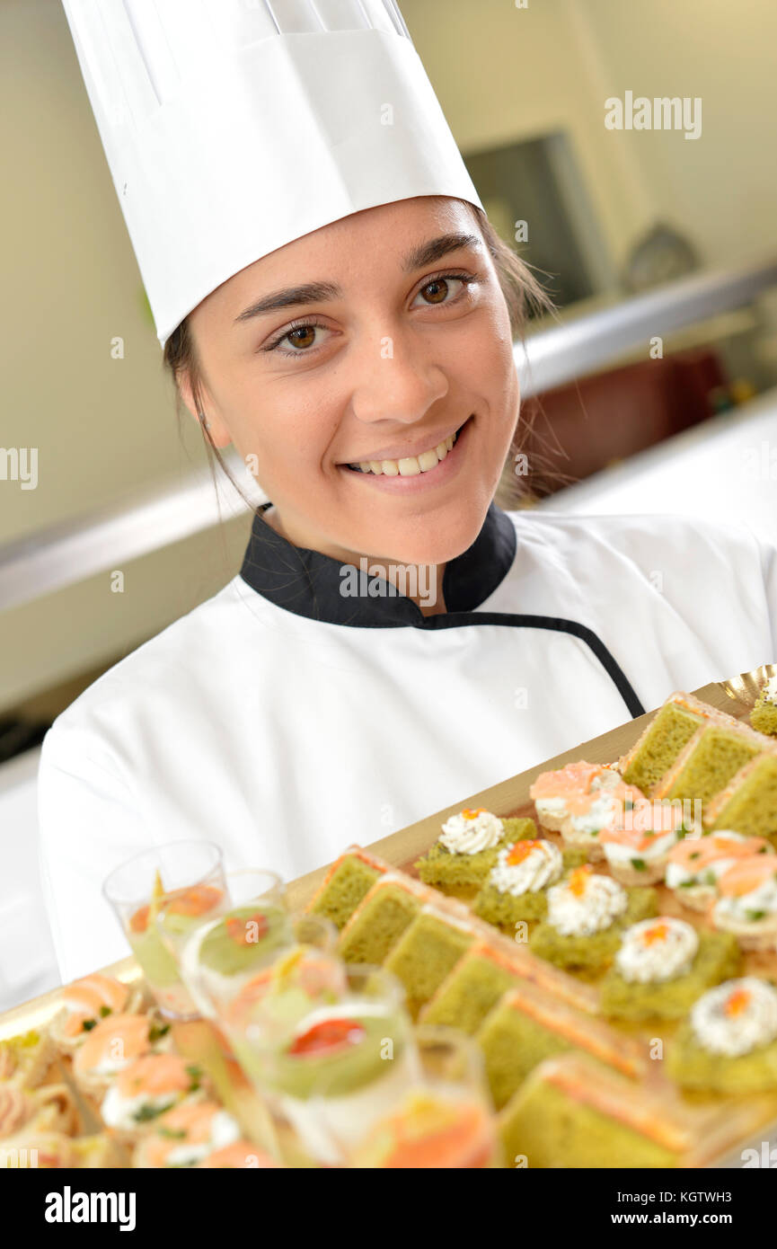 Cheerful young cook holding plate of delicatessen - Stock Image