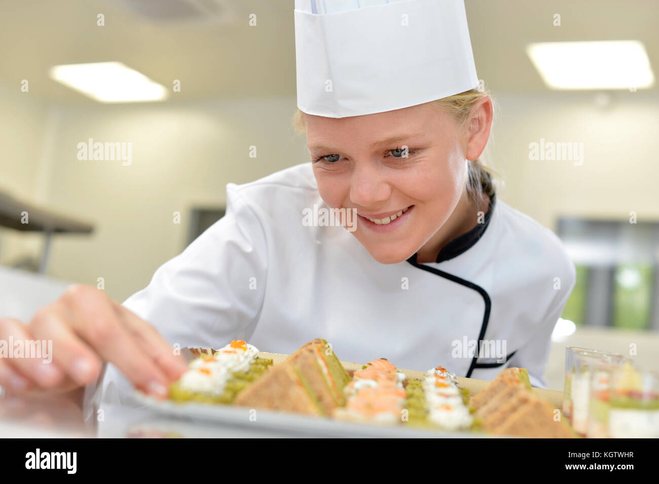 Young caterer preparing tray of appetizers - Stock Image