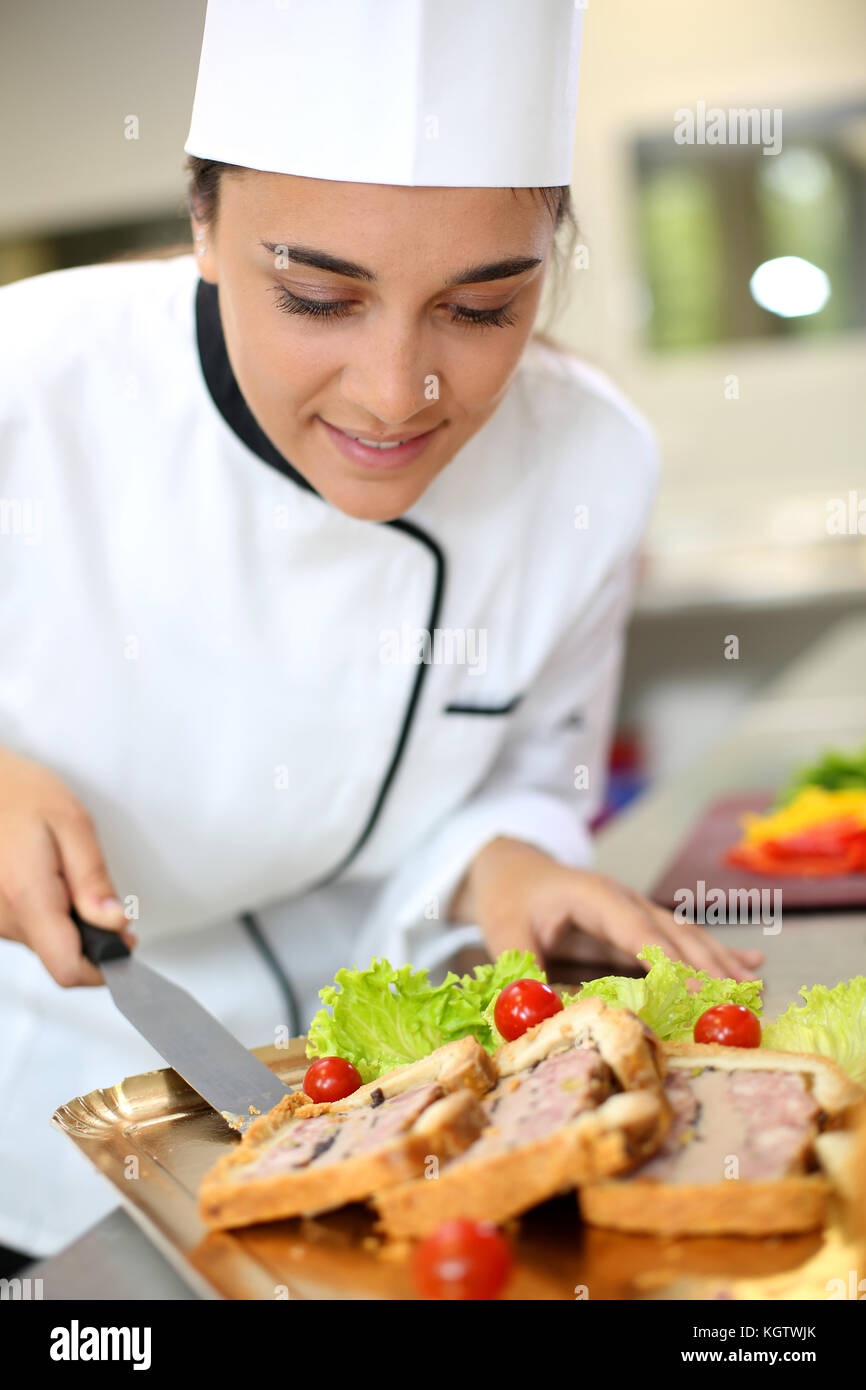 Portrait of beautiful young caterer preparing food tray - Stock Image