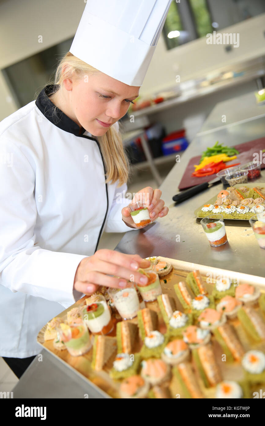 Young caterer preparing tray of appetizer - Stock Image