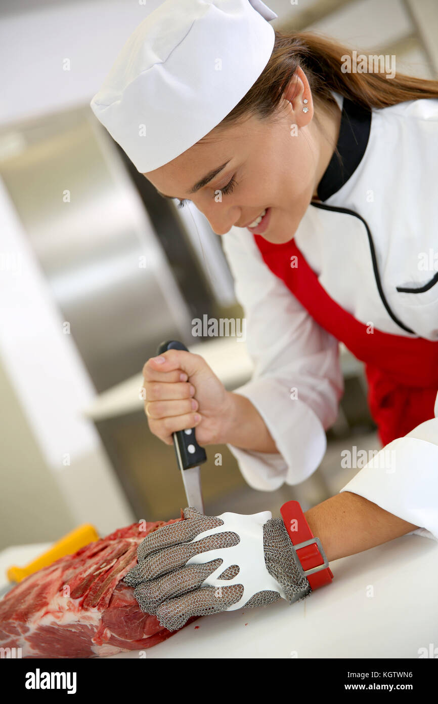 Butcher girl at work cutting ribs - Stock Image