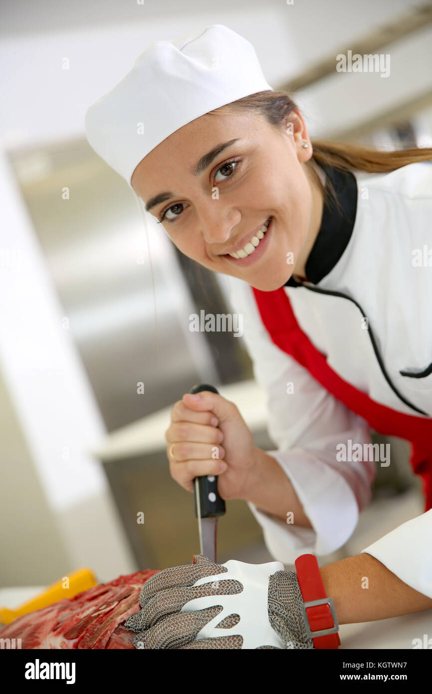 Smiling young butcher girl at work - Stock Image