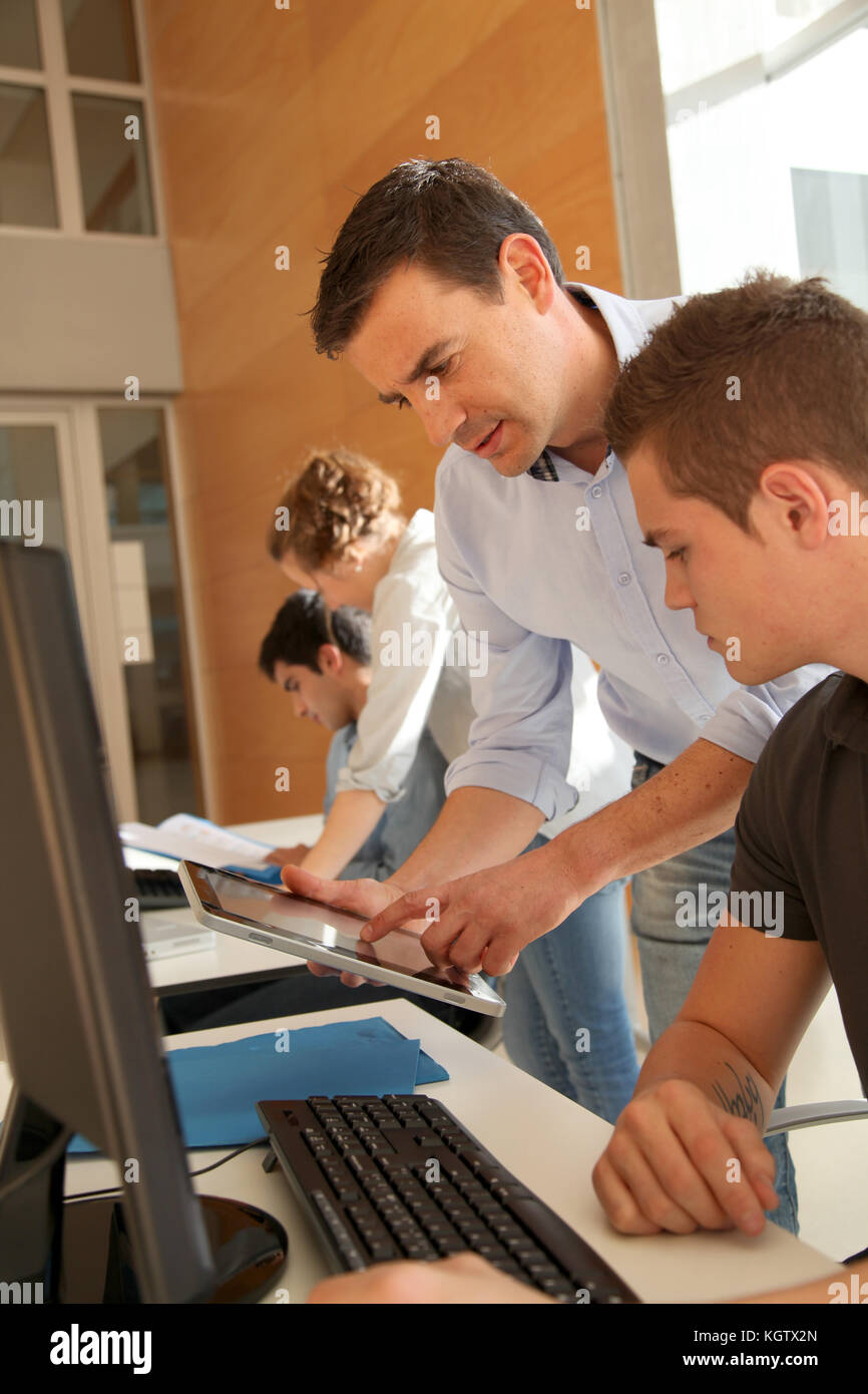 Educator helping student in training class - Stock Image