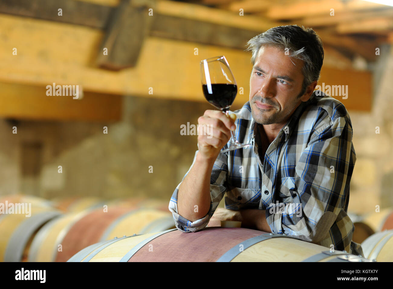 Winemaker tasting red wine in winery - Stock Image