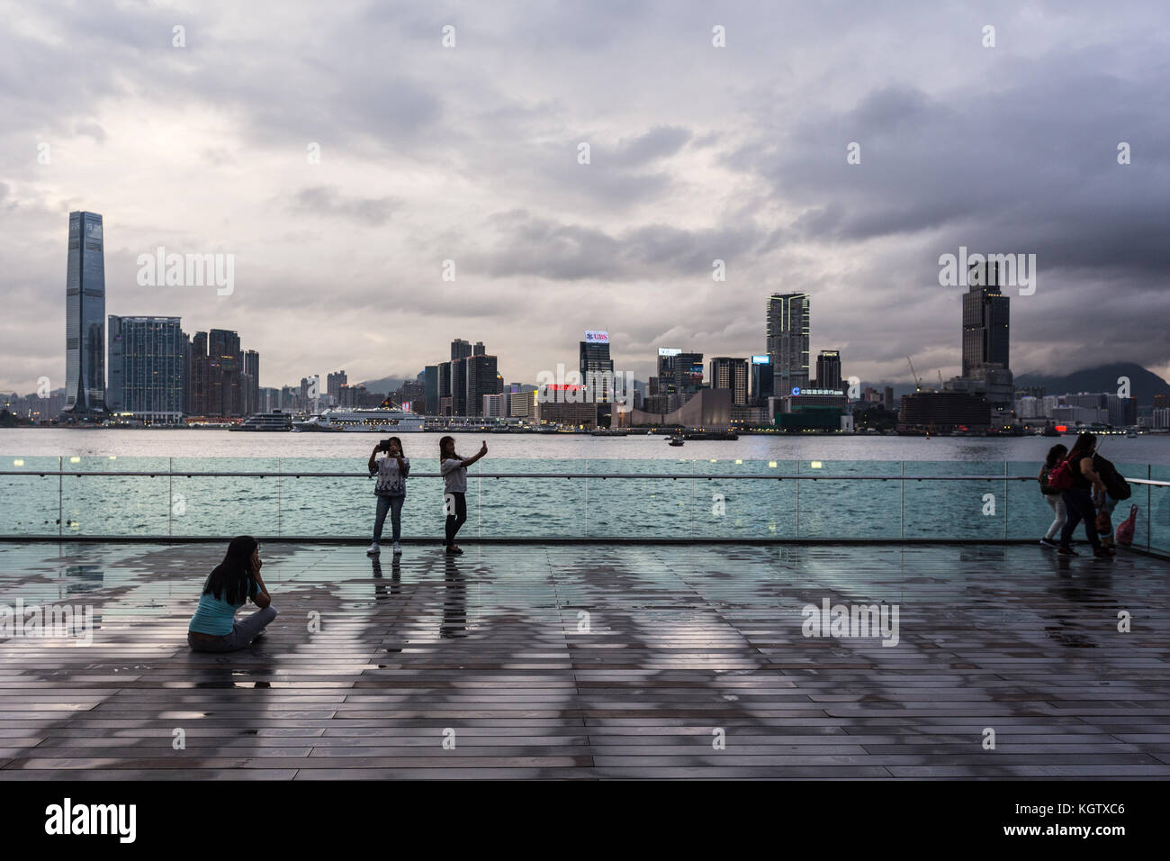 HONG KONG, CHINA - JUNE 16, 2017: Two young Asian women take a selphie with their smartphone in front of the Kowloon - Stock Image
