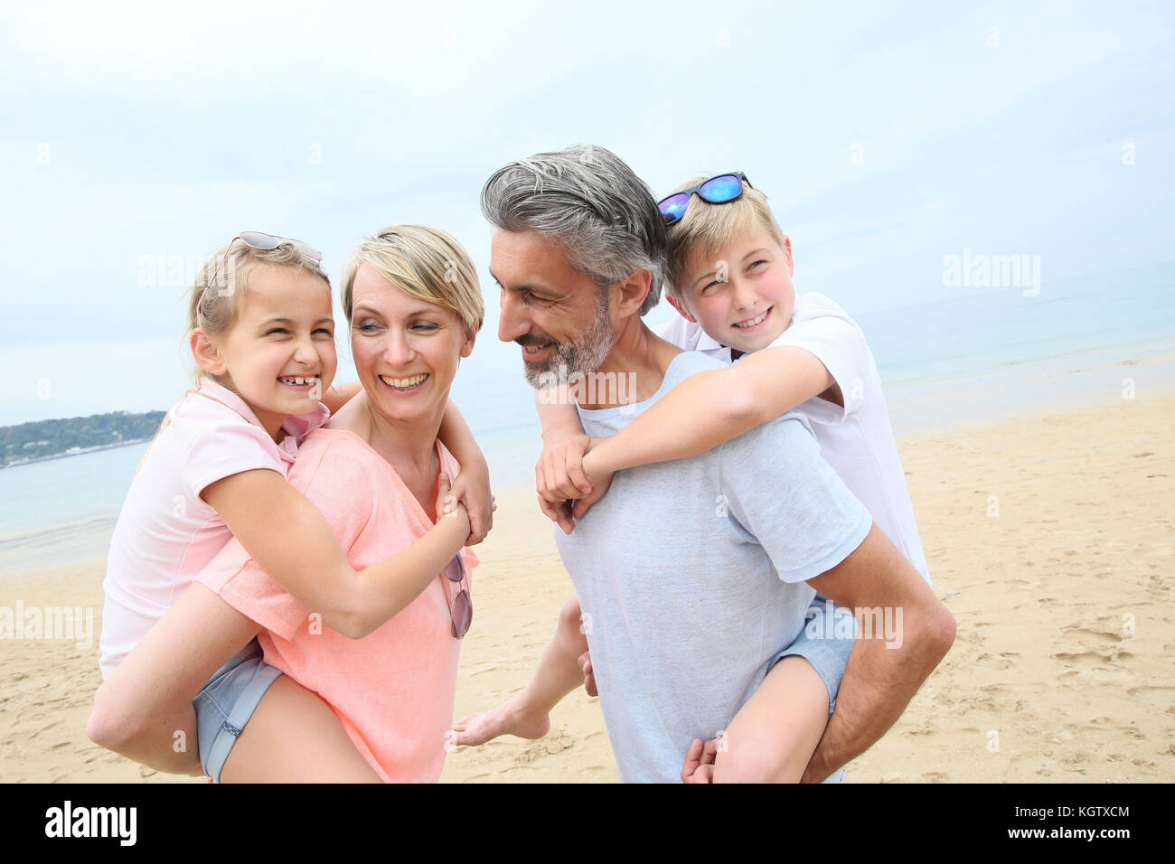 Parents giving piggyback ride to children at the beach - Stock Image