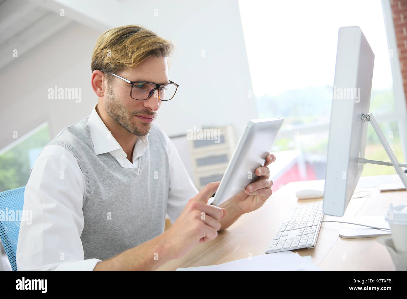 Man in office working on digital tablet, wearing eyeglasses - Stock Image