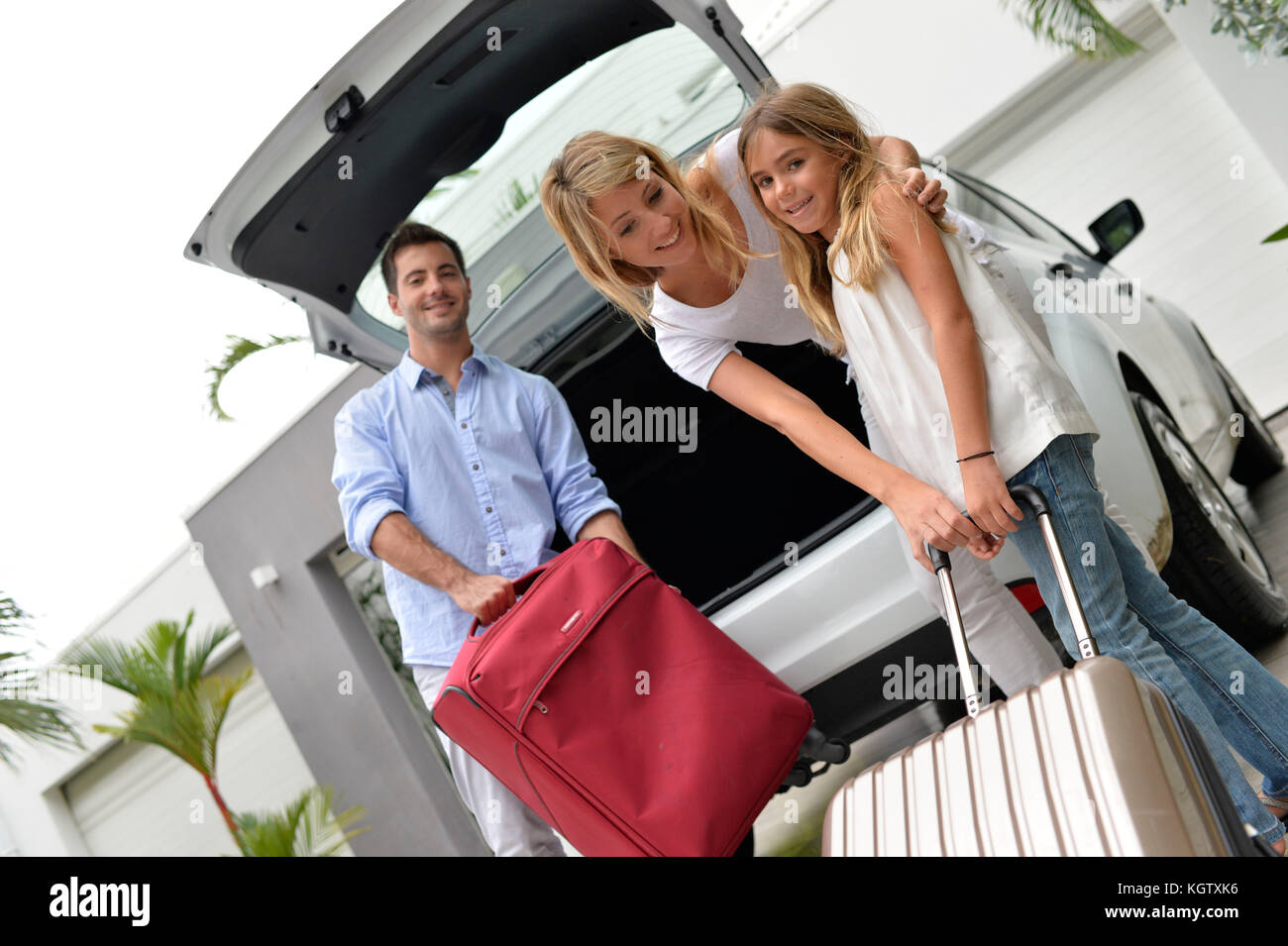 Parents with child putting luggage in car trunk - Stock Image