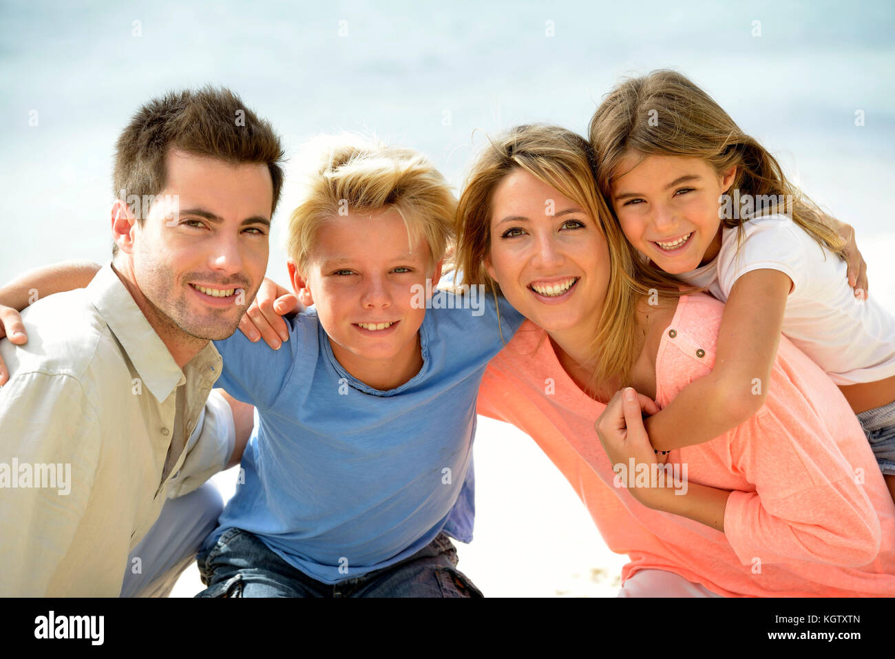Cheerful parents holding kids on their back - Stock Image