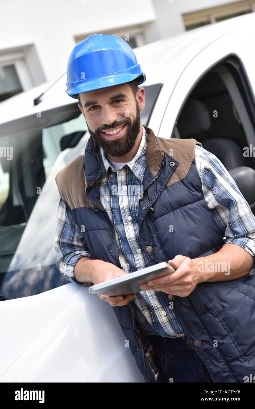 Technician standing by van and using tablet - Stock Image