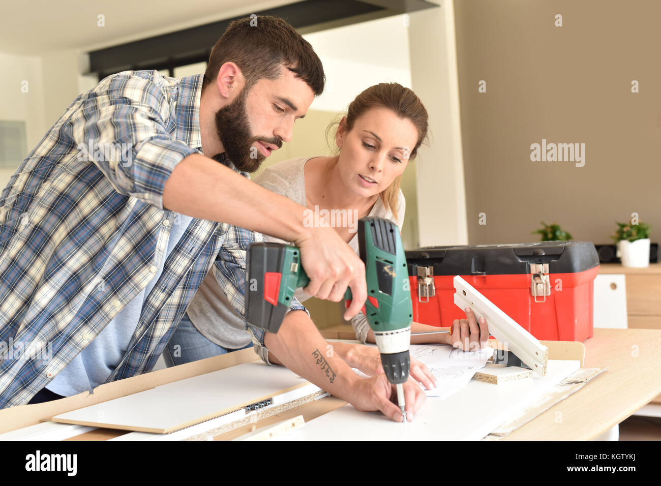 Couple assembling new furniture - Stock Image