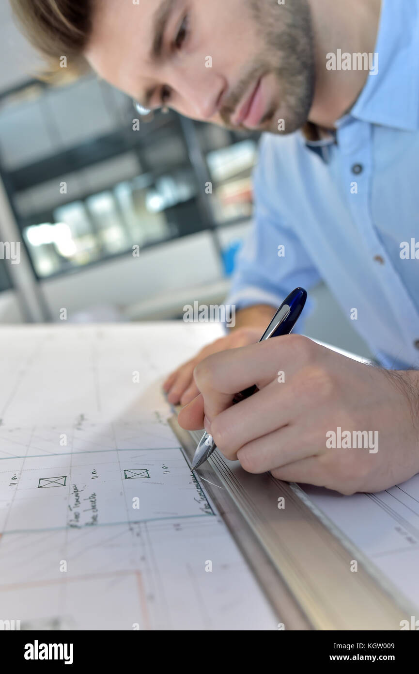 Architect designing on drafting table - Stock Image
