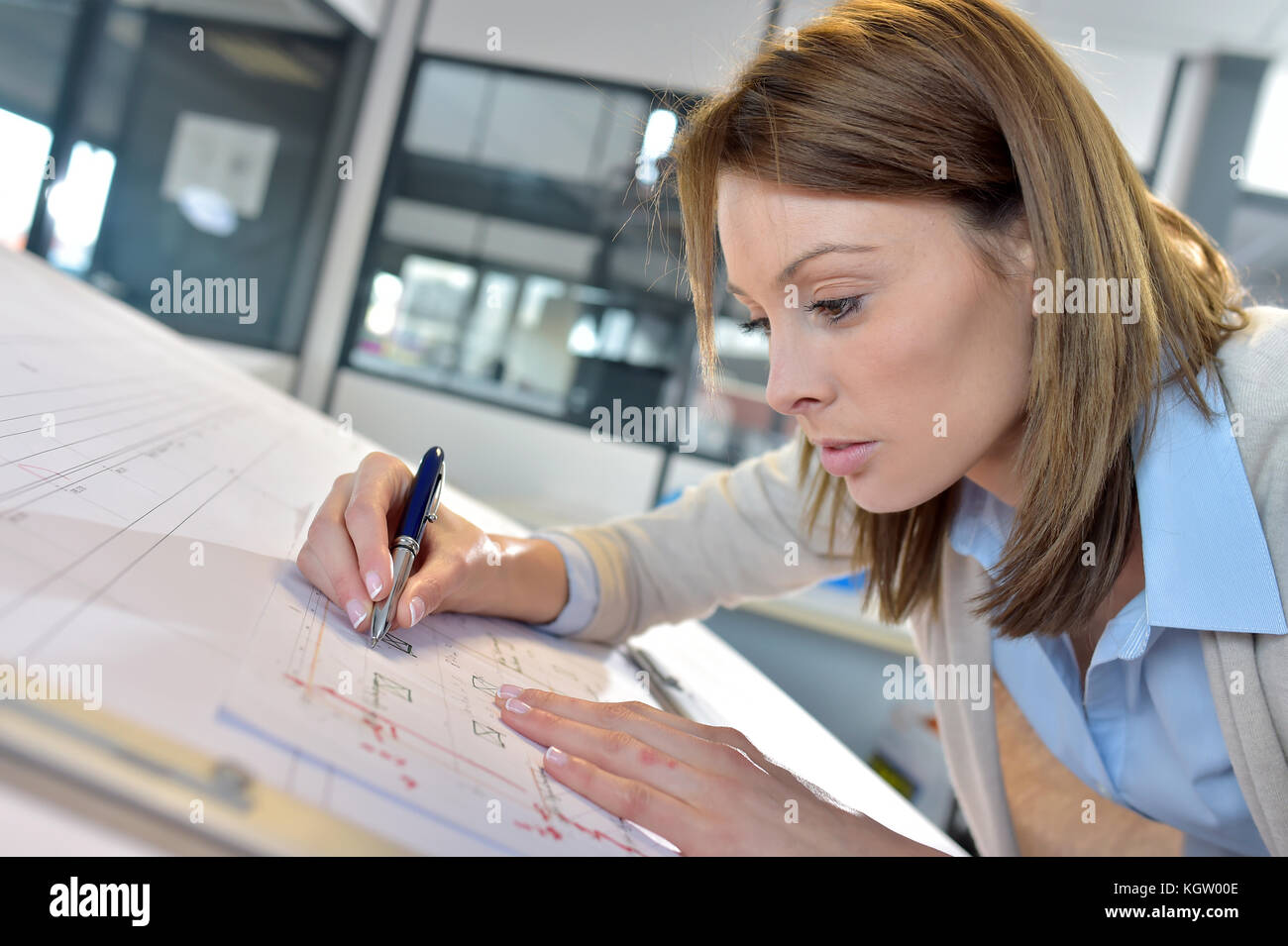 Woman engineer working on blueprint in office - Stock Image