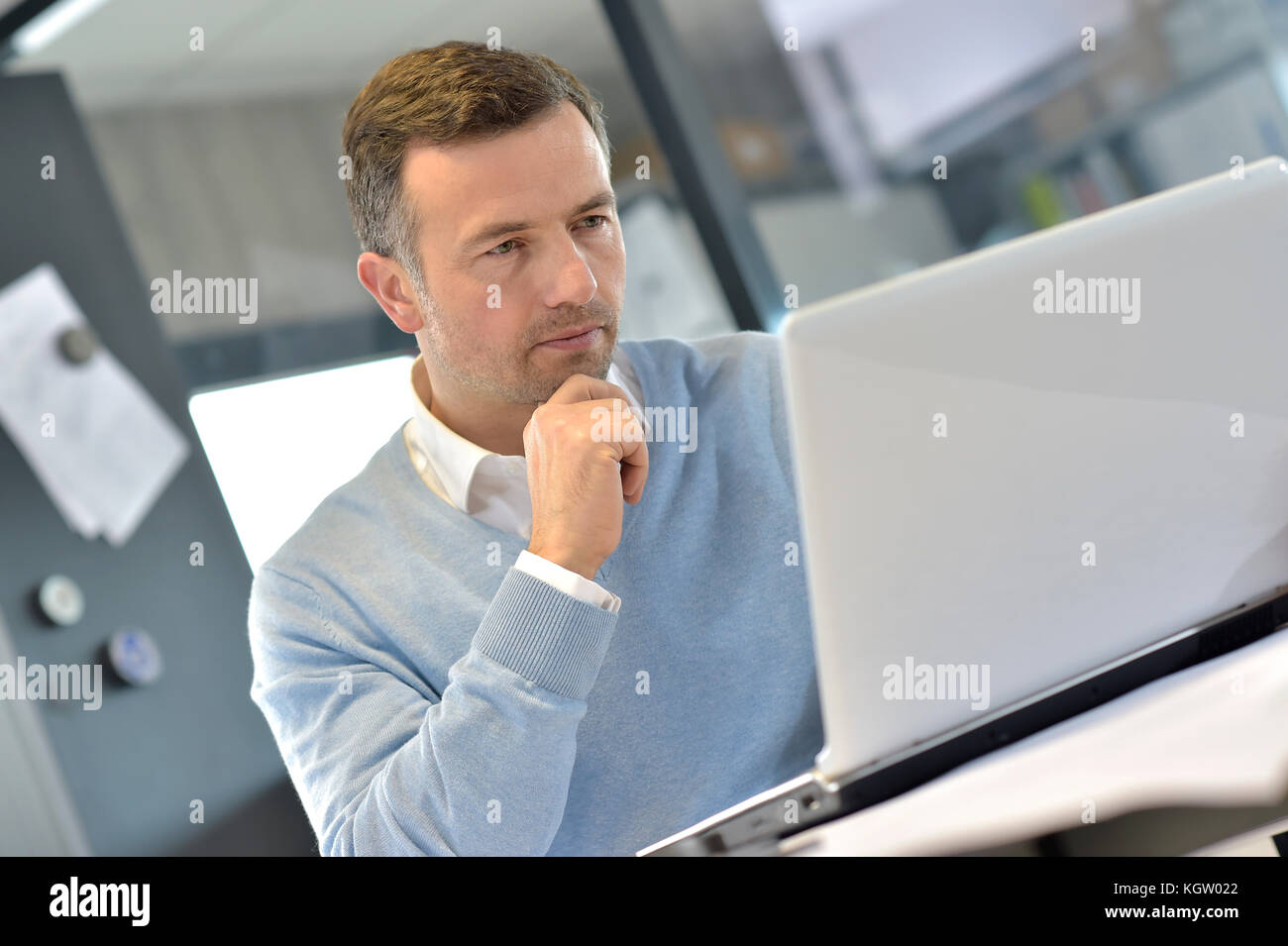 Industrial manager in office working on laptop - Stock Image