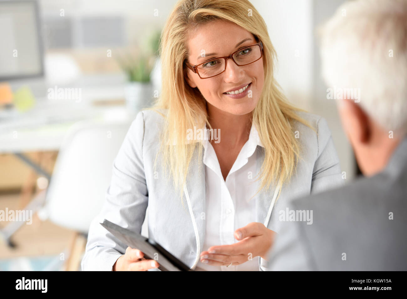 Businesswoman with client in business meeting - Stock Image