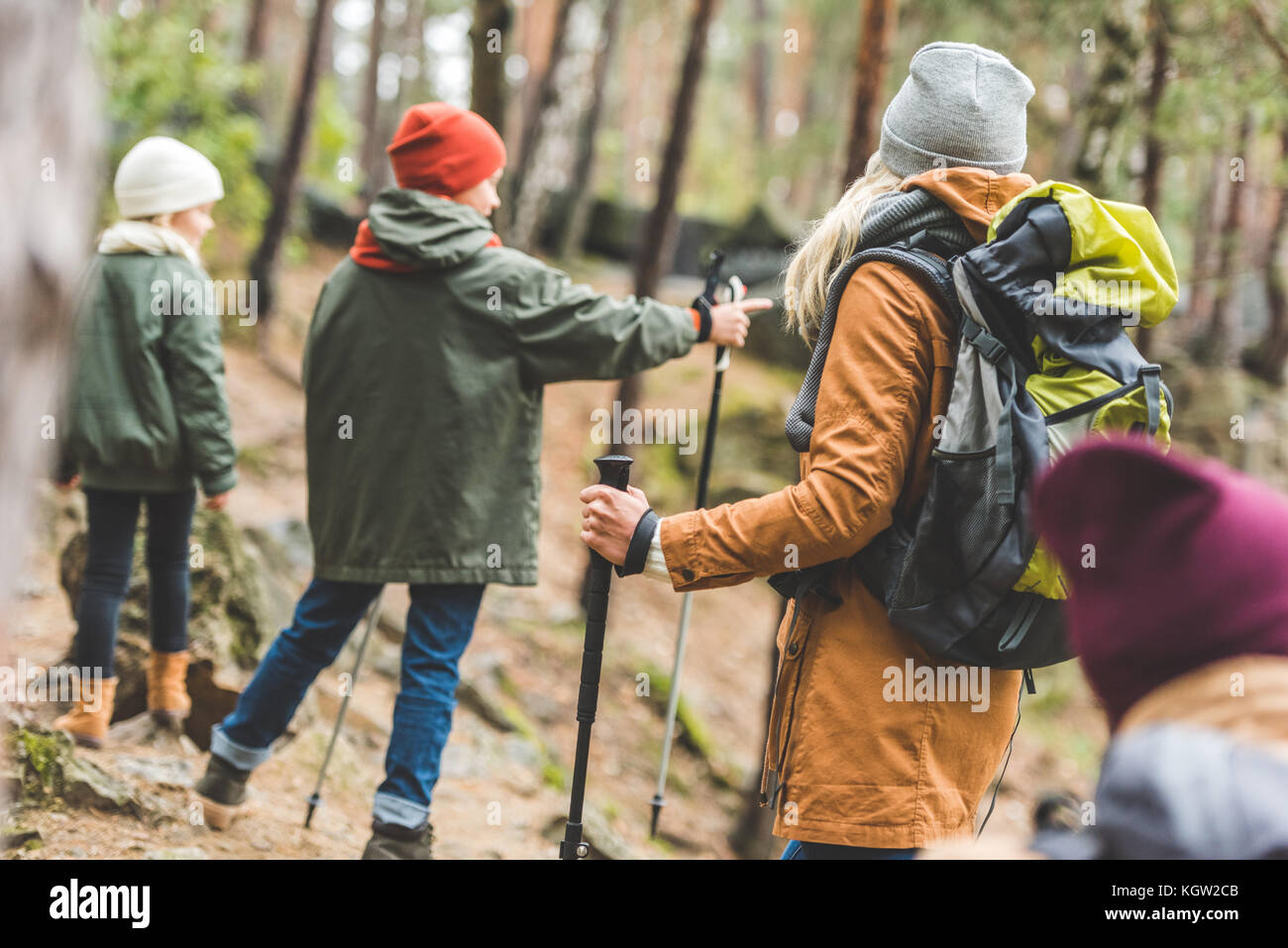 parents and kids trekking in forest - Stock Image