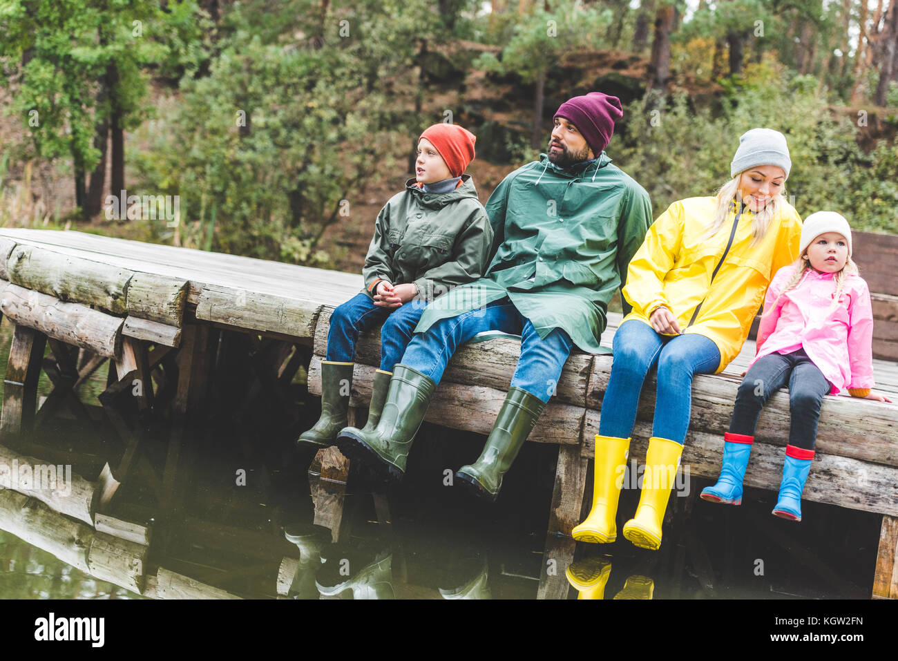 family resting at river - Stock Image